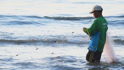 Local fisherman gathering his nets on Kamala Beach. Phuket Footage