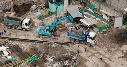 Excavators loading soil and rocks into dump trucks at construction site Footage