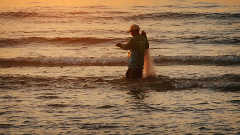 Local fisherman gathering his nets at sunset. on Kamala Beach. Phuket Footage