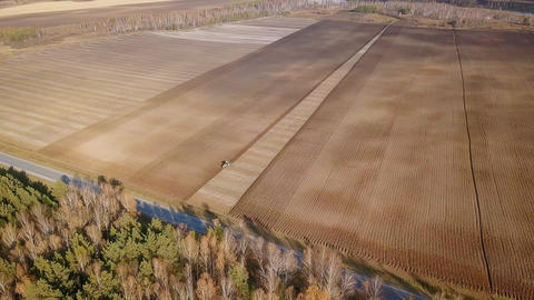 The tractor plows a field with fertilizers. Autumn, Russia, From Dron, Point of Footage