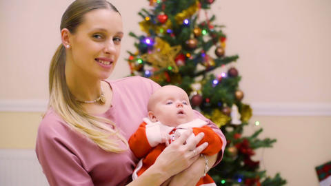 Young mother with adorable little daughter near Christmas tree Footage