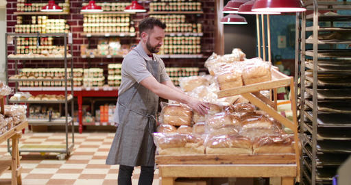 Baker in bakery stocking shelves and looking to camera Footage