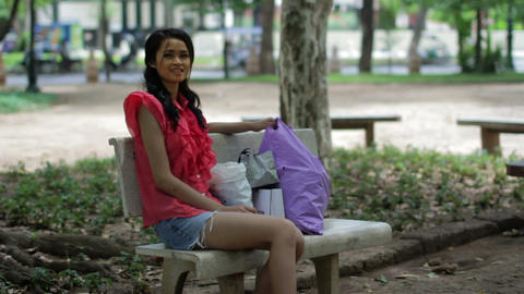Asian girl resting bank bench Stock Video Footage
