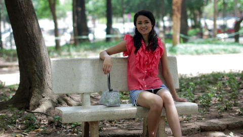 Asian girl sitting bank bench Stock Video Footage