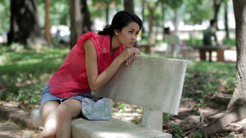 Depressed girl sitting park bench Stock Video Footage