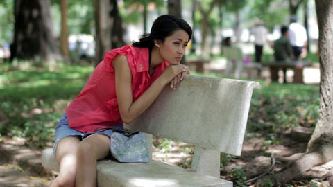 Depressed girl sitting park bench Footage