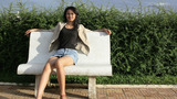 Asian Girl Sitting Bank Bench stock footage