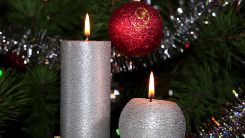 candle lit in front of festive lights Christmas tree Stock Video Footage