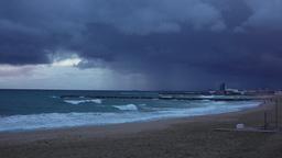 Heavy rain clouds over Balearic Sea shore, waves break on Barcelona beach Footage