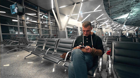 Traveler waits his flight at the waiting hall of the airport, man travels by air Live Action