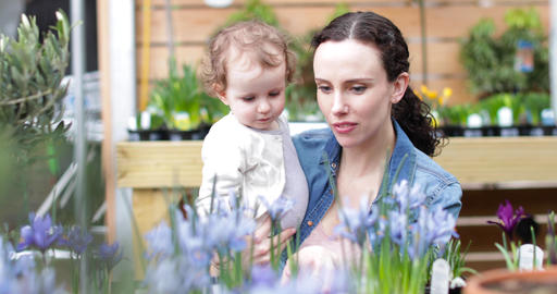 Mother with daughter at garden centre Footage