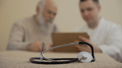 Stethoscope in close-up, doctor with patient at the background Footage