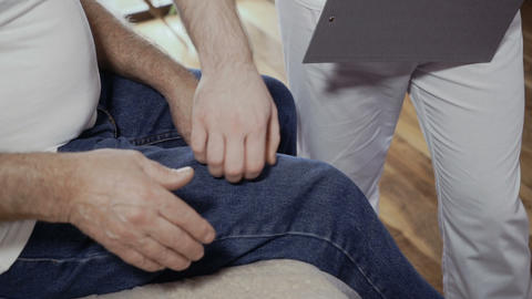 Doctor examines place of pain on patient's leg Footage