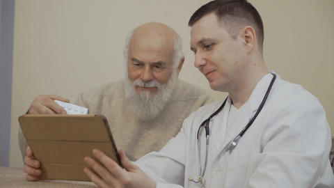 Senior man holds a plate of pills asking something in doctor with digital tablet Footage