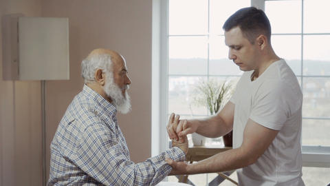 Masseur check pain in the wrist of senior man Footage