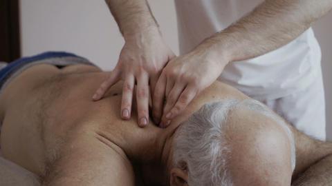 Masseur massages shoulder of senior man Footage