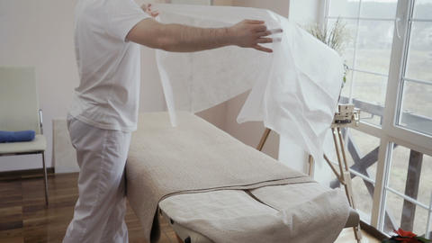 Doctor cover couch with disposable sheet in slowmotion Live Action