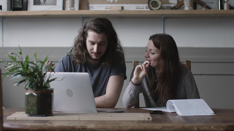 Young adult couple using a working on finance application together Footage