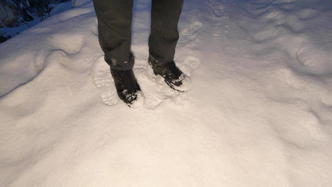 Man legs in dark trousers and high outdoor boots walking in snow while heavy Filmmaterial