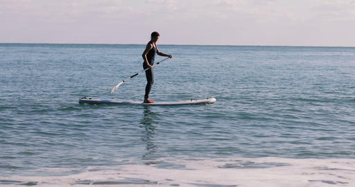 Female practice paddle boarding in the sea 画像