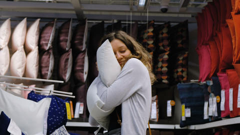 Young girl chooses a pillow at the Mall, 4K Live Action