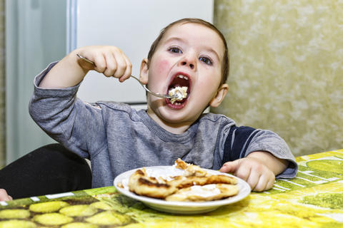 The little boy is eating. Concept: healthy child, happy childhood Fotografía