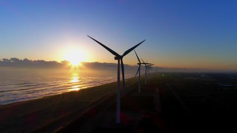 Aerial - Sunrise and coastal wind power plant ビデオ