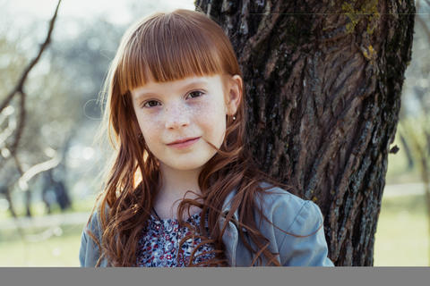 happy red-haired little girl leaned against a tree Foto
