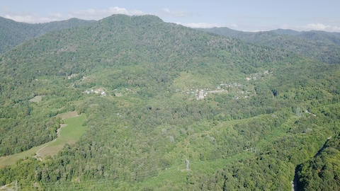 The mountains are covered with forest and village. There is an electric Footage