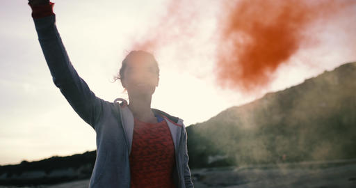 Young adult female holding smoke grenade and skateboarding GIF