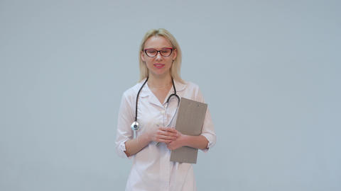Female doctor with white coat and stethoscope smiling looking into camera Footage