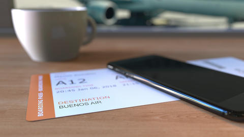 Boarding pass to Buenos Aires and smartphone on the table in airport. Travelling Footage