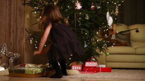 A little girl runs to open a Christmas present under the tree Footage