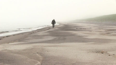 A Man Walks Along the Sandy Beach Footage
