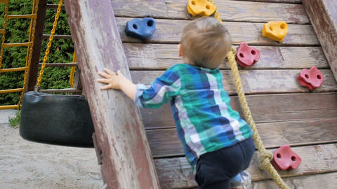 Slow motion video of toddler boy trying to climb on wooden wall at playground in Footage