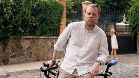 4k video of confident bearded man in white shirt posing with bicycle on old Footage