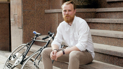 4k footage of stylish red bearded man with vintage bicycle sitting on stone Footage