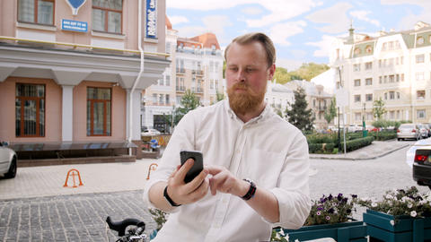 4k footage of stylish bearded man leaning on his bibcyle and using smart phone Footage