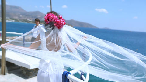 Bride groom on beach after their wedding with the bride's veil blowing with the Footage