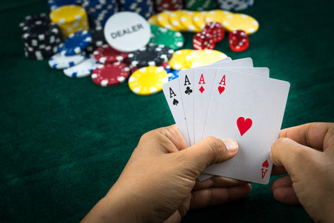 Gambling Hand Holding Poker Cards and Money Coins Chips Fotografía