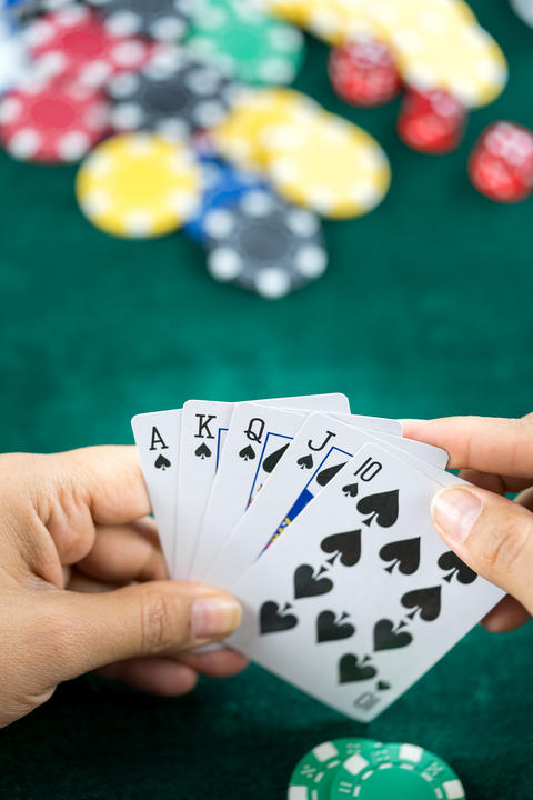 Gambling Hand Holding Poker Cards and Money Coins Chips Photo
