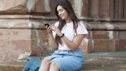 4k panning footage of beautiful smiling girl typing message on mobile phone Footage
