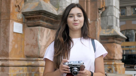 Slow motion footage of young smiling woman making photographs while walking on Footage