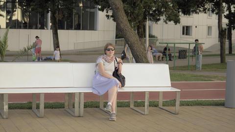 Pretty girl seats on the bench in park , Batumi, Georgia Archivo