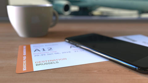 Boarding pass to Brussels and smartphone on the table in airport while Footage