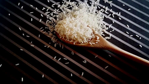 Pouring rice on the table and wooden black-and-white spoon ビデオ