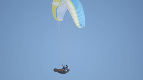 The pilot of the paraglider hovers in the air. Pilot paraglider against the blue Live Action