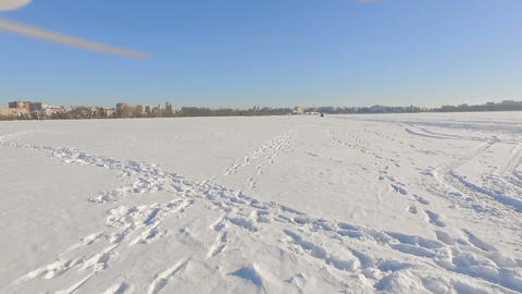 drone flies over a frozen lake near a city park in the background of a winter Bild