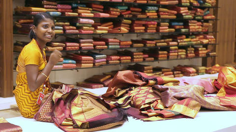 Woman Holds Sari and Talks to Customers against Shelves Footage
