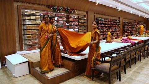 Indian Girls Show Customers Orange Sari Cloth in Store Footage